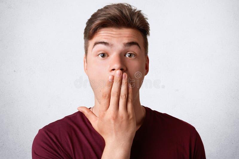 Headshot van zwaar verrast mannetje behandelt mond en kijkt met verbazing, probeert sprakeloos te zijn, stelt tegen witte backrou royalty-vrije stock afbeeldingen
