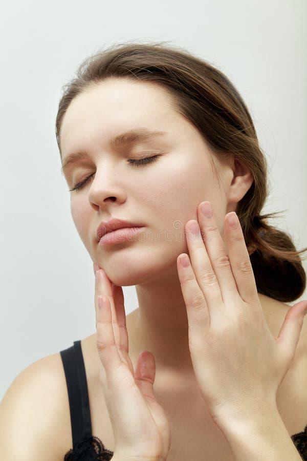 Headshot vertical de jeune modèle femelle avec les yeux fermés se faisant le massage facial photo libre de droits