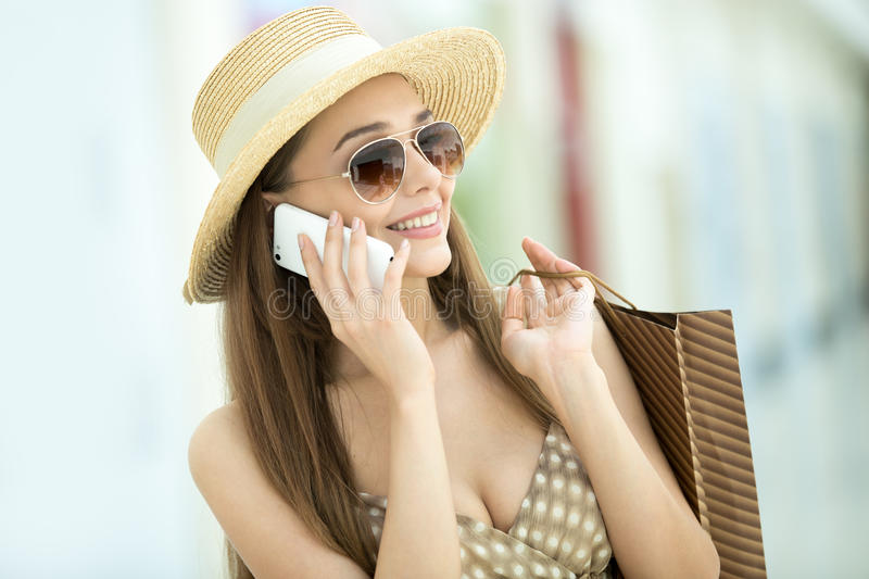 Headshot of woman in shopping centre talking on mobile phone. Headshot portrait of young pretty woman standing in shopping centre, wearing hat and sunglasses royalty free stock image