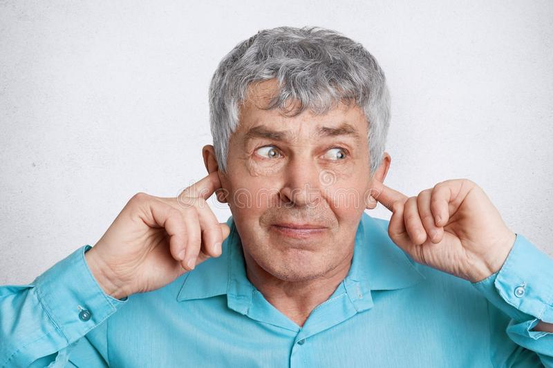 Headshot of wrinkled elederly male with grey hair plugs ears as doesn`t want hear something, looks with unhappy expression away, i royalty free stock image