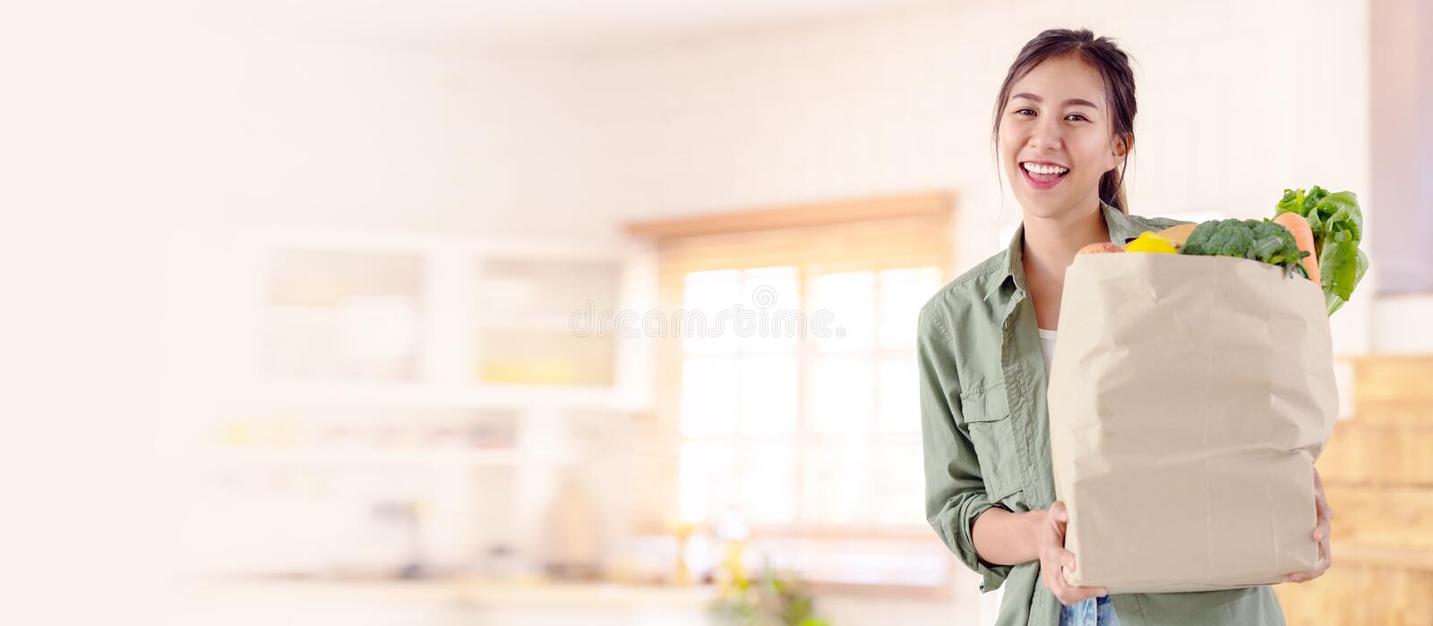 Headshot of young attractive asian girl, housewife or single lady holding groceries paper bag looking and smiling to camera in royalty free stock photo