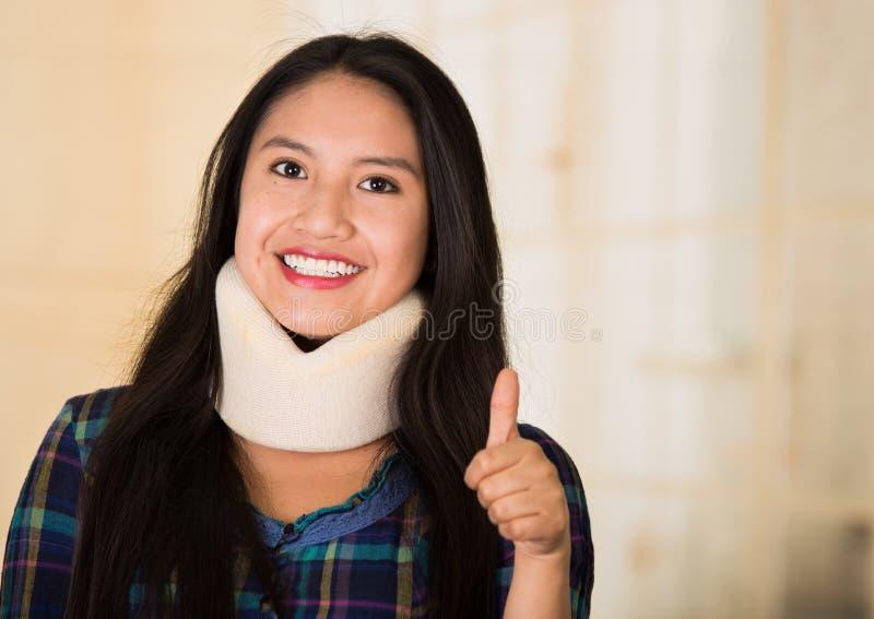 Headshot young hispanic woman posing wearing neck brace, smiling happily giving thumb up to camera, injury concept.  royalty free stock photo