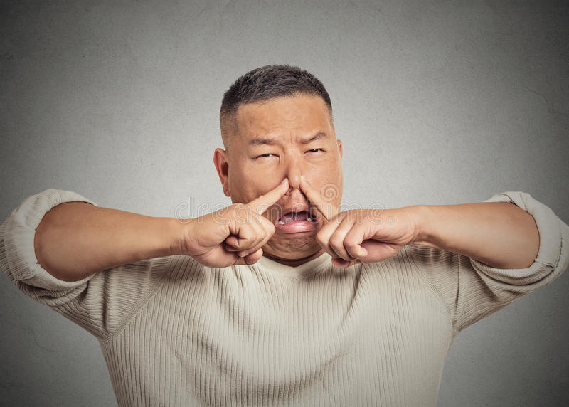 Headshot young man disgust on face, pinches nose something stinks stock photo