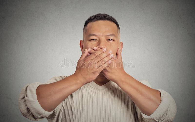 Headshot young man student worker employee covering his mouth. Closeup portrait headshot young man student worker employee covering his mouth with hands. Speak royalty free stock photo