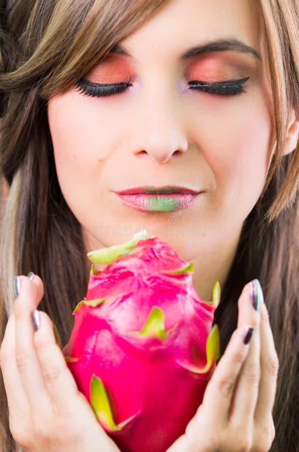 Headshotbrunett, mörk nimbusblick och gräsplanläppstift, hållande övre rosa pitayafrukt med båda händer som vänder mot kameran fotografering för bildbyråer