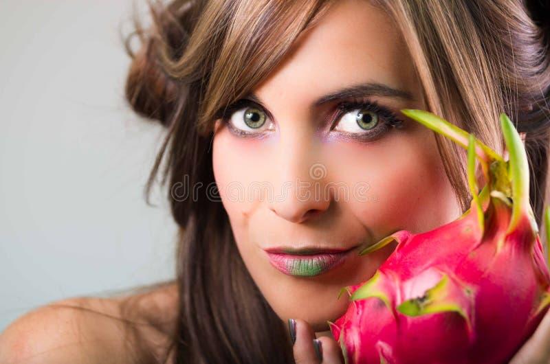 Headshotbrunett, mörk nimbusblick och gräsplanläppstift, hållande övre rosa pitayafrukt som ser in i kamera fotografering för bildbyråer