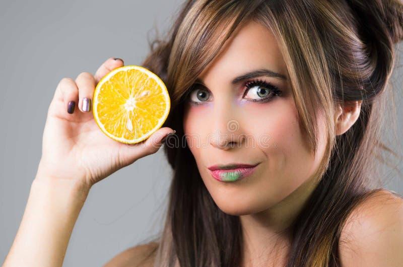 Headshotbrunett med mörk nimbusblick- och gräsplanläppstift som är hållande övre en apelsin bredvid framsidan som ser in i kamera arkivfoto