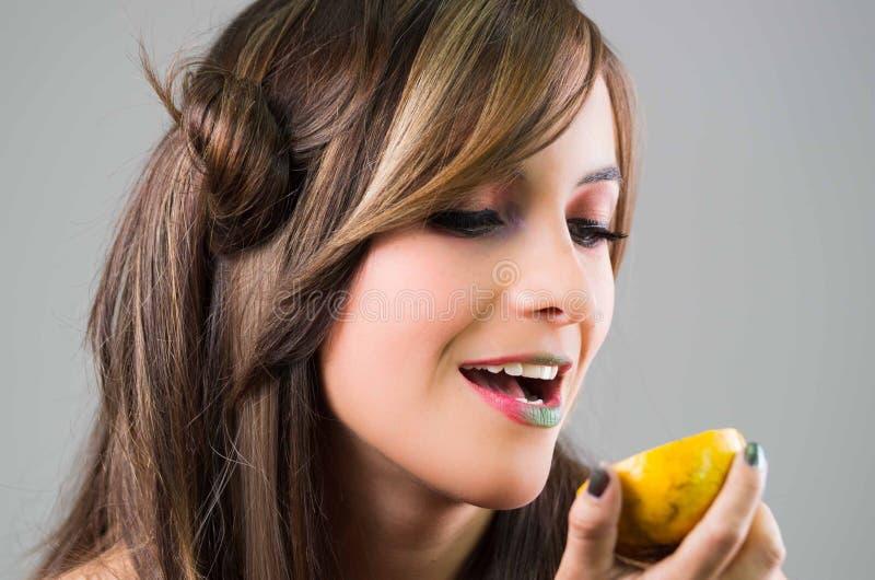 Headshotbrunett med mörkt hållande övre för nimbusblick- och gräsplanläppstift en apelsin, grå bakgrund royaltyfria bilder