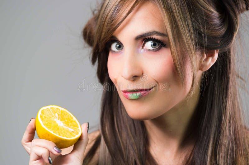 Headshotbrunett med mörkt hållande övre för nimbusblick- och gräsplanläppstift en apelsin, grå bakgrund arkivfoto