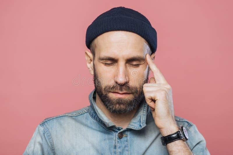 Headshoten av den allvarliga fundersamma mitt åldrades mannen försöker att minnas något i hans mening, främre finger för uppehäll royaltyfri bild