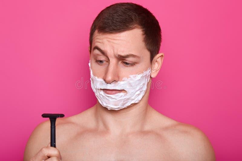 Headshoten av den stiliga mannen ser gästgivargårdförvirring på rakkniven, har att raka stelnar på kinder, har daglig rutin i bad arkivbilder