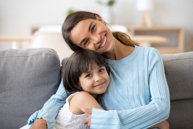 Headshotmulattmoder och dotter som sitter tillsammans att se arkivbild