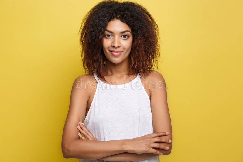 Headshotporträt der schönen attraktiven Afroamerikanerfrauenaufgabe kreuzte Arme mit dem glücklichen Lächeln Gelbes Studio lizenzfreie stockfotografie