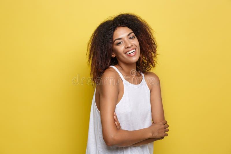 Headshotporträt der schönen attraktiven Afroamerikanerfrauenaufgabe kreuzte Arme mit dem glücklichen Lächeln Gelbes Studio stockfotos