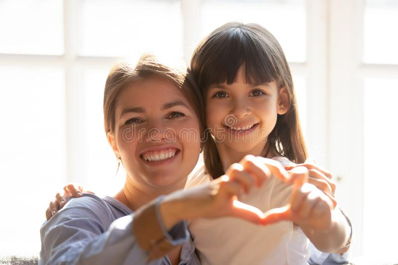 Headshotporträtmutter und -tochter machen Herzform mit den Händen stockfotografie