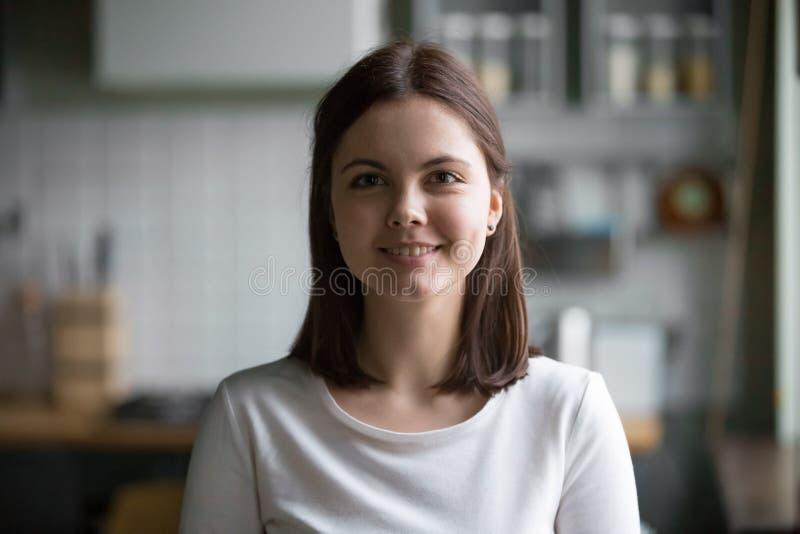 Headshotstående av att le den millennial kvinnan som poserar den hemmastadda satsen royaltyfri bild