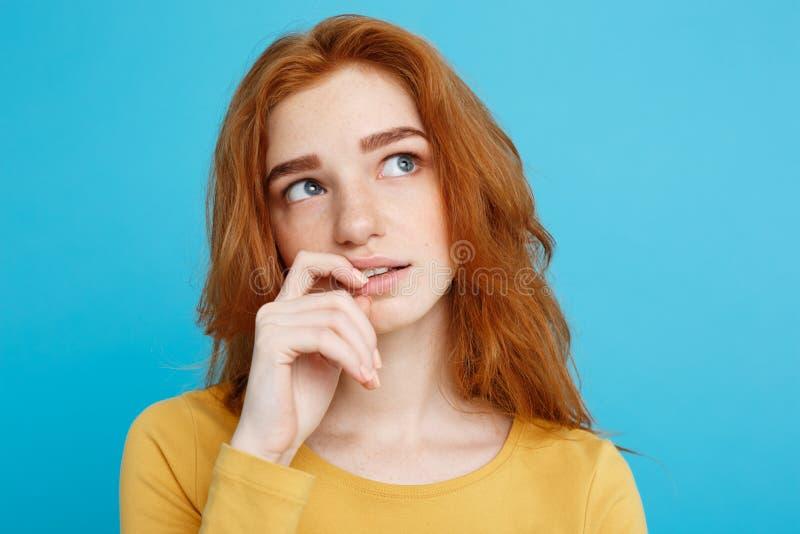 Headshotstående av den lyckliga ljust rödbrun röda hårflickan med fräknar som ler se kameran Pastellfärgad blåttbakgrund kopia arkivbilder