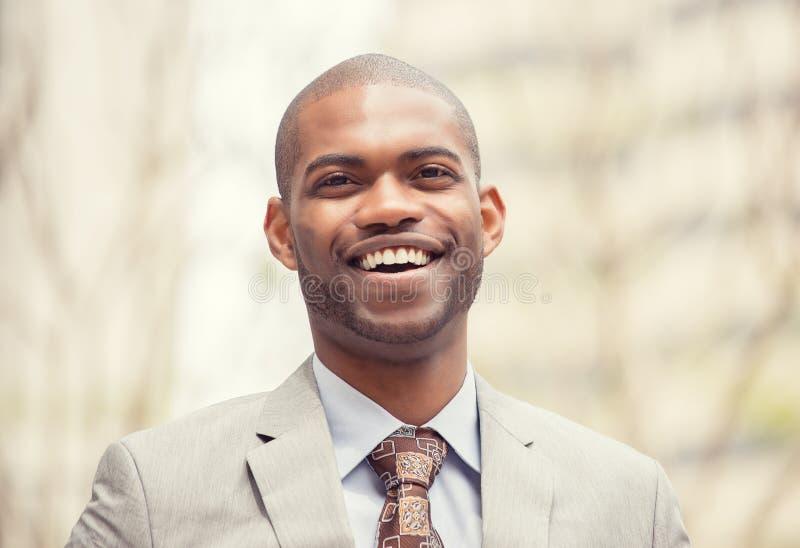 Headshotstående av den unga yrkesmässiga mannen som ler att skratta royaltyfri foto