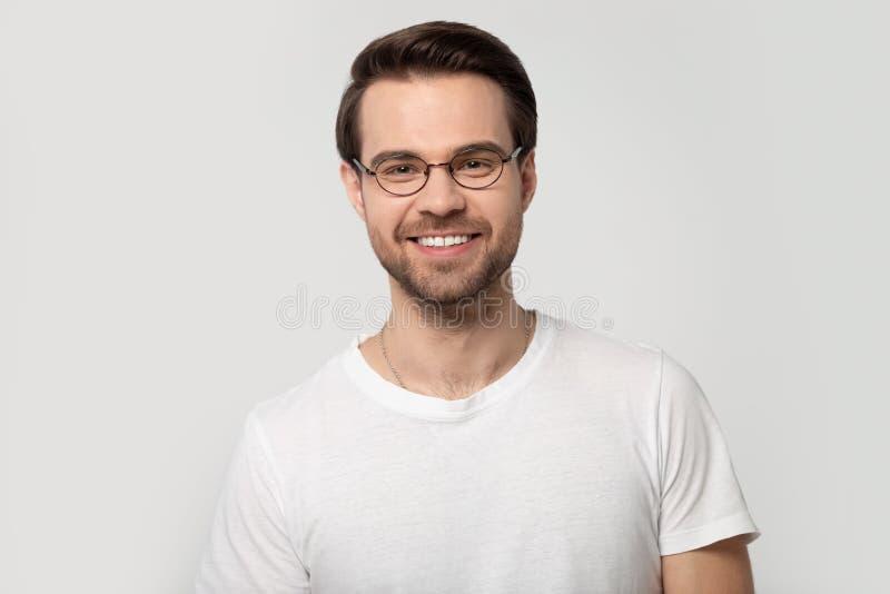 Headshotstående som ler bärande exponeringsglas för man på grå bakgrund royaltyfri fotografi