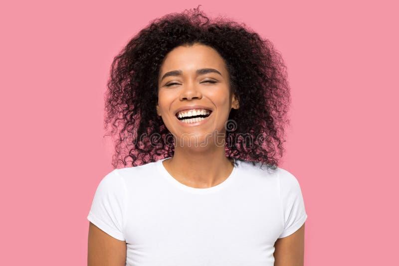 Headshotst?ende som skrattar den afrikanska kvinnan p? rosa bakgrund royaltyfria foton