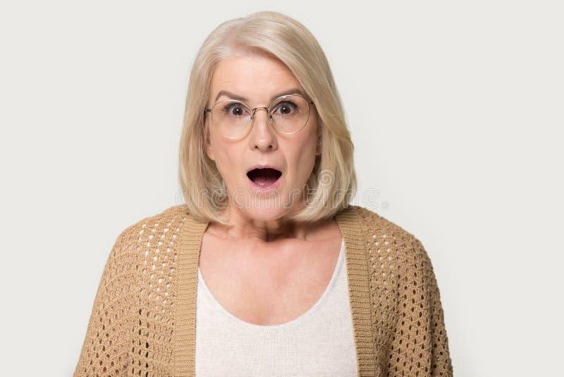 Headshotstudioståenden åldrades den häpna chockade kvinnan som isolerades på grå färger arkivbild