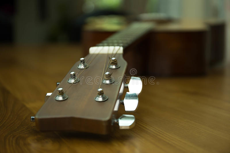 Headstock of accoustic guitar. On wooden table royalty free stock photos