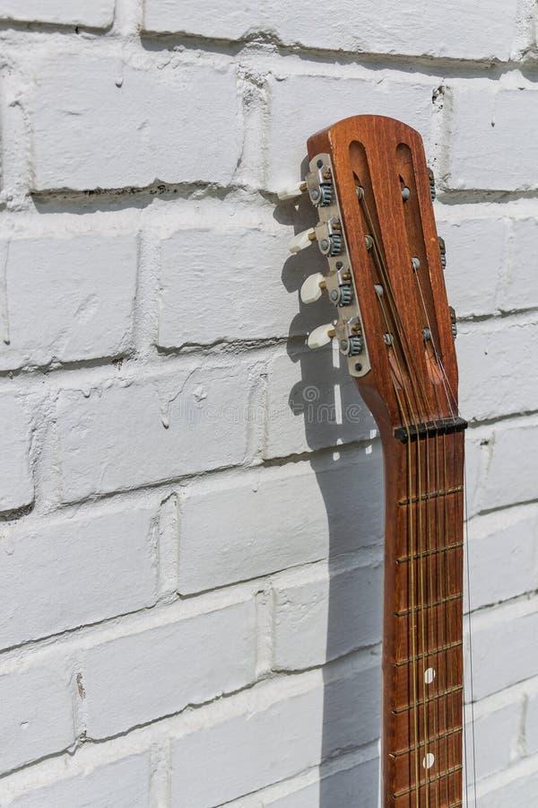 Headstock da guitarra acústica contra a parede de tijolo branca foto de stock