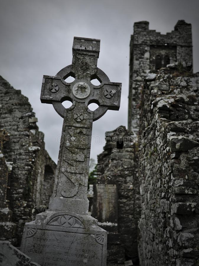 Headstone with celtic cross on a cemetery with church ruins in the background royalty free stock image