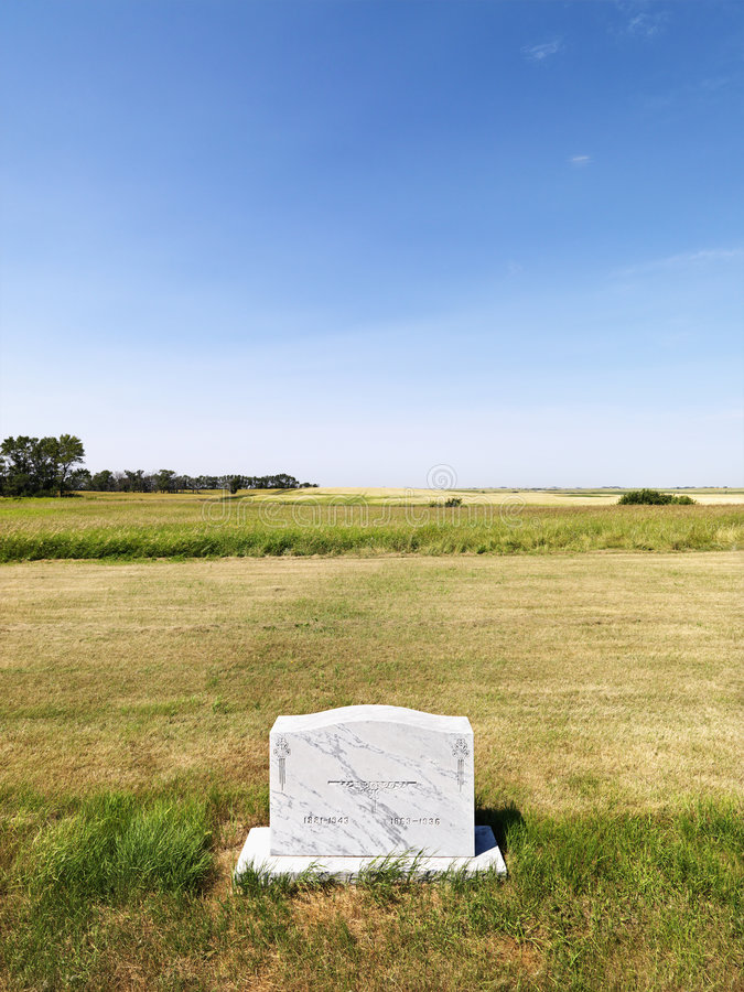 Headstone in field. royalty free stock photography