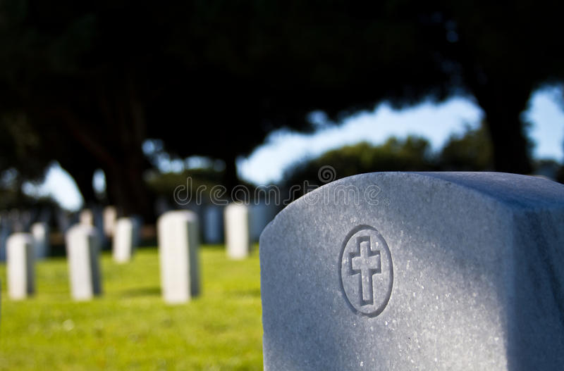Headstone in morning sunlight. Morning sunlight in a graveyard with a close up of a shadow across a foreground headstone stock photo