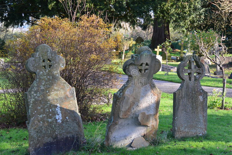 Headstone trio. Three old gravestones in an English churchyard royalty free stock image