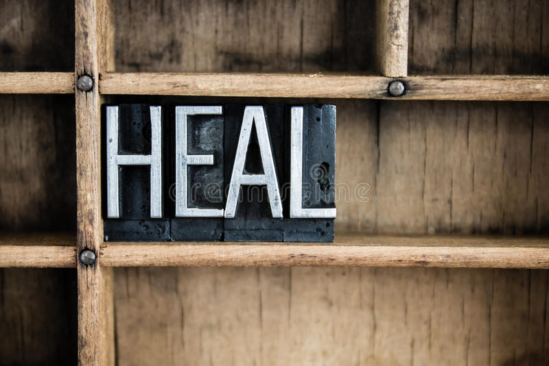 Heal Concept Metal Letterpress Word in Drawer. The word HEAL written in vintage metal letterpress type in a wooden drawer with dividers stock images