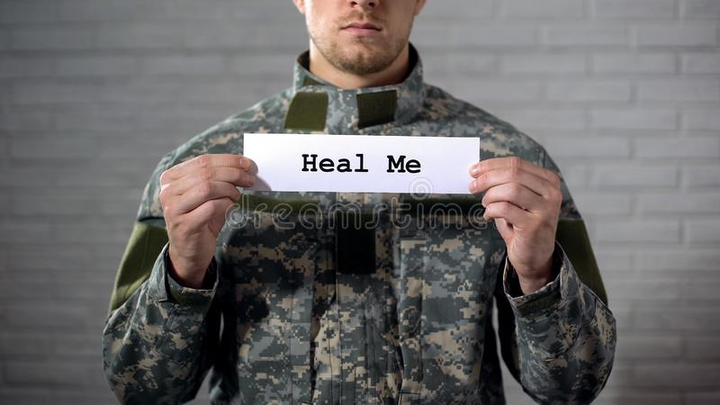 Heal me word written on sign in hands of male soldier, social security, rehab. Stock photo stock photos