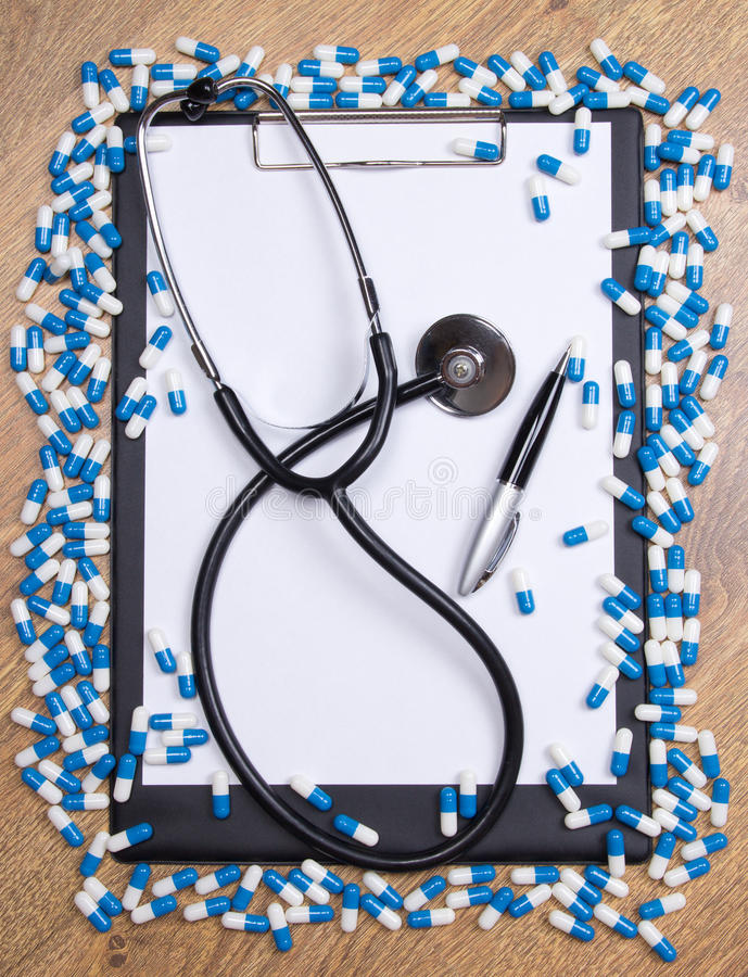 Heal of tablets, clipboard, stethoscope and pen on wooden table. Heal of blue tablets, clipboard, stethoscope and pen on wooden table royalty free stock photos