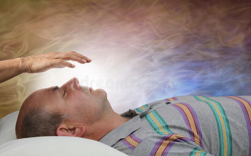 Healer Channelling White Healing Energy. Female with hand held a few inches above a male patient`s face against a flowing ethereal energy formation background stock photos