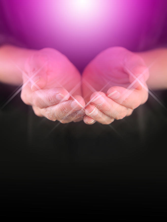 Healer with Magenta Healing Orb Energy. Female holding hands in cupped position with a bright magenta colored orb energy hovering above and sparkles around royalty free stock image