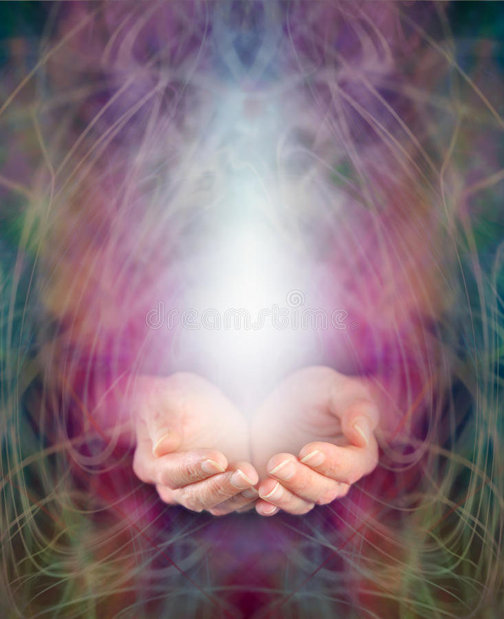 Healer's cupped hands and energy manifestation. Healing hands cupped with swirling energy and white light emerging royalty free stock image