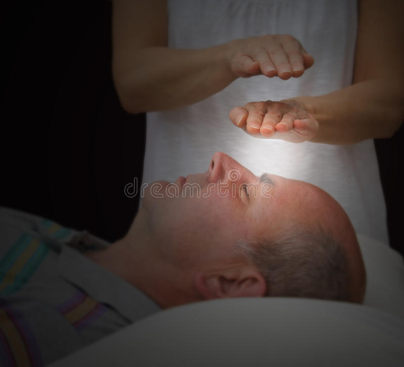 Healer Sensing Aura Levels. Female healer with hands sensing male supine patient's third eye chakra aura levels on a black background stock image