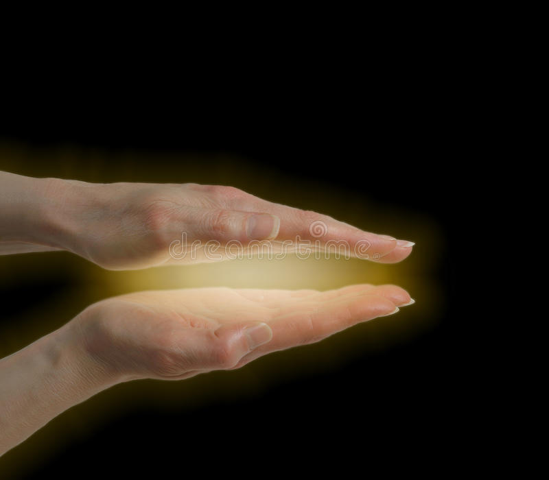 Healer sensing energy field. Woman's healing hands in parallel position with golden healing energy between on black background royalty free stock images