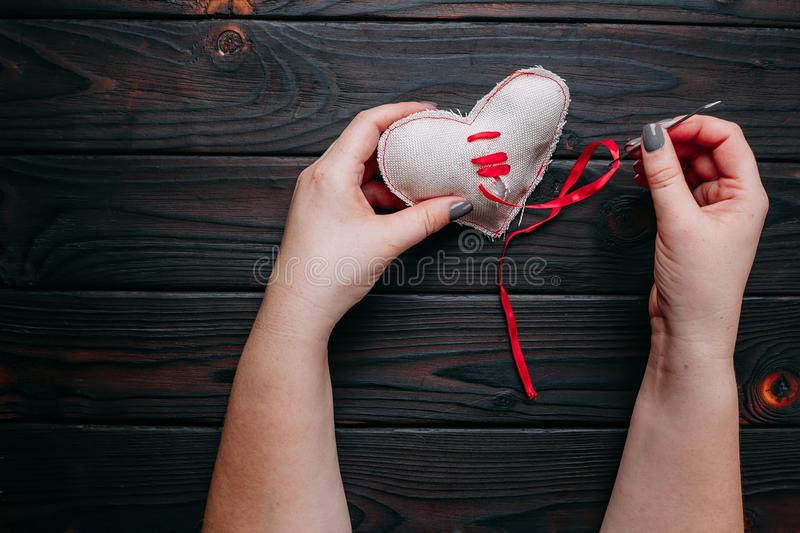 Healing broken heart. Hands sewing a fabric heart with a needle. With a red ribbon . Psychology, love, relationship, Valentines day, help concept royalty free stock images
