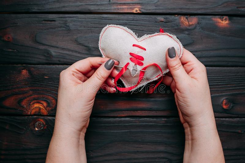 Healing broken heart. Hands sewing a fabric heart with a needle. With a red ribbon . Psychology, love, relationship, Valentines day, help concept stock image