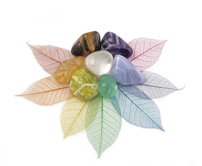 Healing Chakra Crystals on Leaves. Seven Healing Chakra Crystals placed in a circle on an arrangement of rainbow colored skeleton leaves cut out on a white stock images