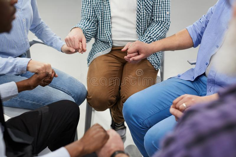 Healing Circle. High angle close up of people holding hands sitting in circle during therapy session in support group, copy space royalty free stock images