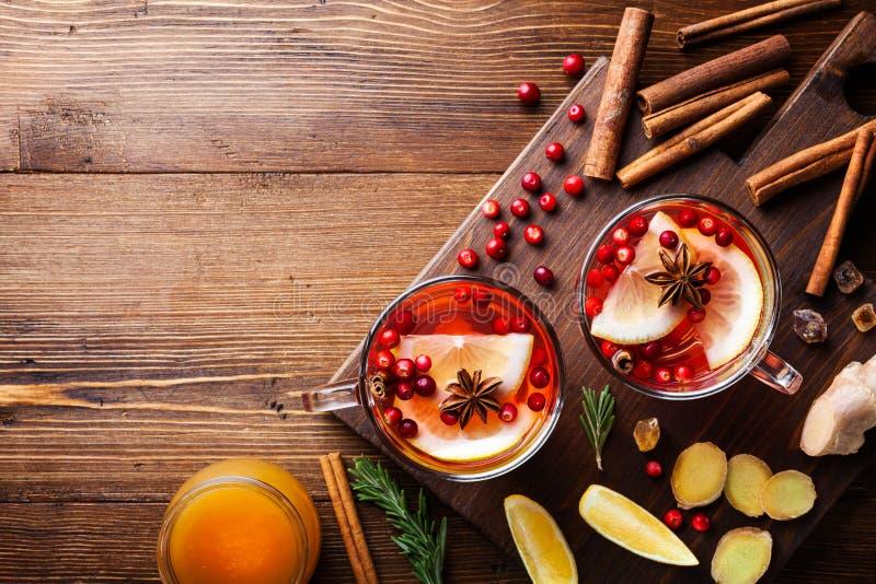 Healing cranberry tea in twee glazen mok met citroen, honing, gember en specerijen Herfst hete drank op bijtende achtergrond bove royalty-vrije stock afbeelding