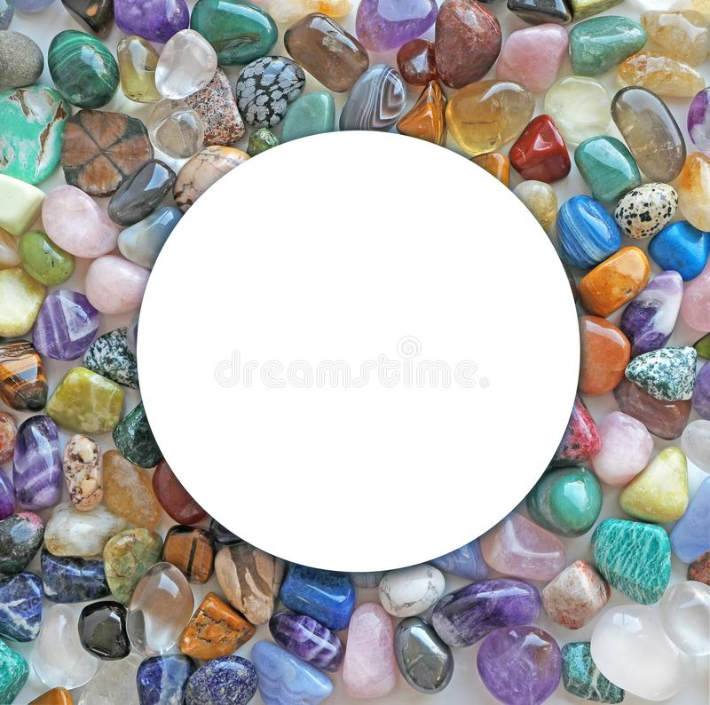 Healing Crystal Circle Surround Border. Sharp edged empty white circle frame surrounded by multicoloured tumbled healing stones royalty free stock photography