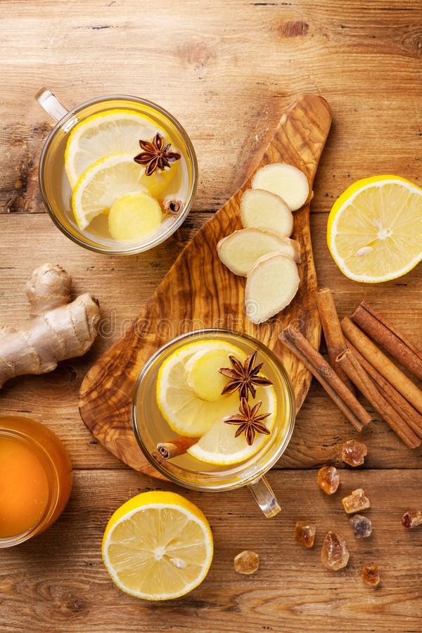 Healing ginger tea in two glass mug with lemon, honey and spices. Autumn hot drink on rustic wooden table top view royalty free stock photos