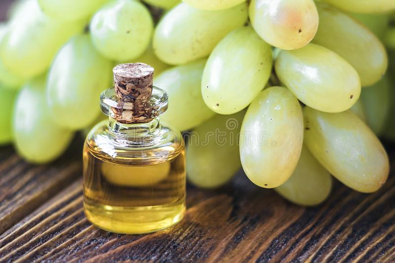 Healing grapes seeds oil in a glass jar, fresh grapes on old wooden background, seed extract has antioxidant and nourishing the sk royalty free stock photography