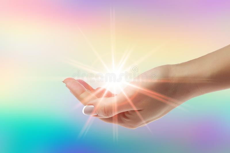 Healing hands with bright sunburst on rainbow background. Women healing hands with bright sunburst on rainbow background stock images