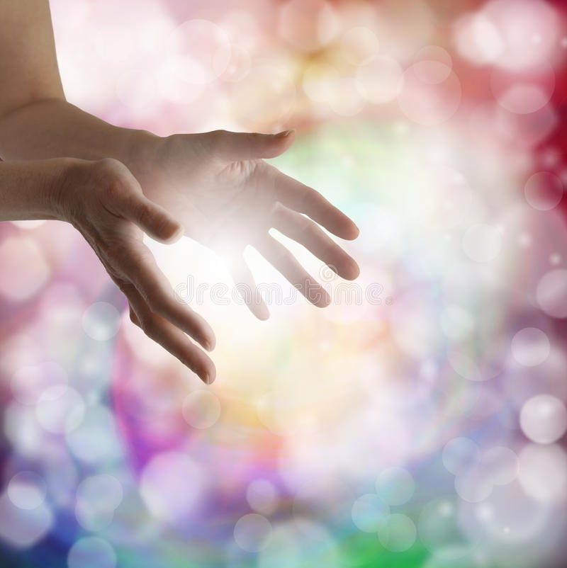 Healing hands and sparkling energy. Woman's outstretched healing hands with light bokeh background and energy ball stock photo