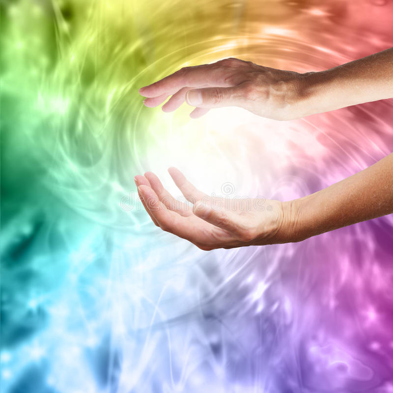 Healing hands with vibrant rainbow vortex stock photo